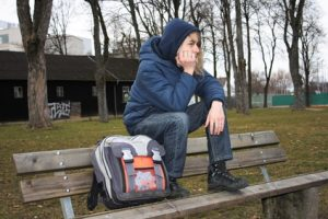 Teenaged boy alone on a bench with backpack