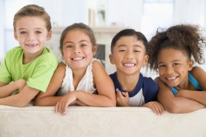four smiling children of mixed ethnicity ages 6 to 10